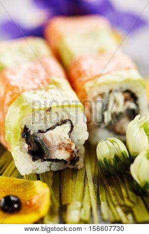 Rainbow Maki Sushi - Roll with Smoked Eel (unagi) and Cream Cheese inside. Salmon and Avocado outside