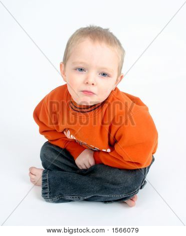 Cute Little Boy Frowning On A White Background