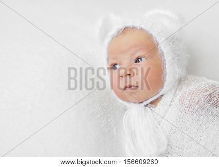 swaddled funny newborn baby in white hat with ears with curious eyes