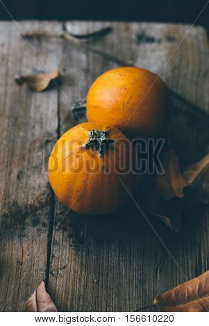 Two tiny ripened pumpkins on a grunge wooden background, dry leaves scattered around it. An artistic spooky effect still life.