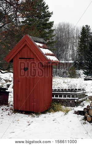 A Red wooden outhouse toilet on wintertime.