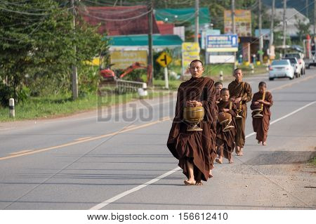 Buddhist monk and young monks walking side of road for given food on morning at Khao-kho, Phetchabun province, Thailand.