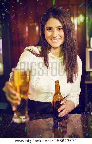Portrait of pretty bartender serving beer at bar counter against flying colours