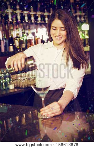 Pretty bartender pouring blue martini drink in glass against flying colours