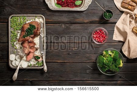 Frame with garnish of rice salad of beets broccoli bread and sauce on a dark wooden table