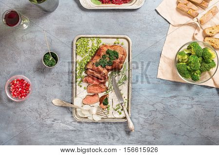 Juicy sliced grilled beef steak on the old iron tray on light stone surface top view
