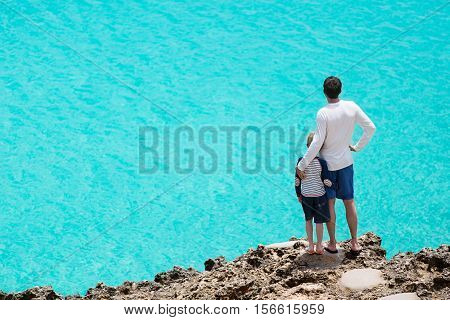 back view of family of two standing at rocky cliff enjoying turquoise caribbean sea vacation and family concept
