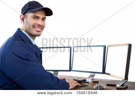 Happy security officer using computer against white background