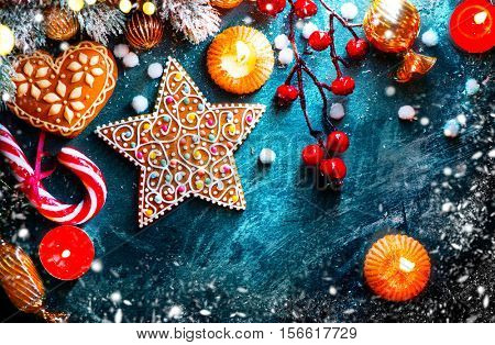 Christmas traditional food, Christmas Holiday Background with ornate Gingerbread cookies, Candy Cane and evergreens border over dark background table. Christmas and New year food. Christmas decoration