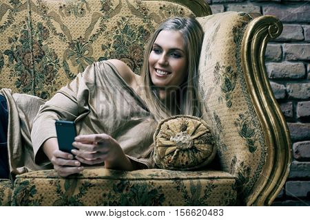 Beautiful young blonde woman using mobilephone resting on sofa, smiling.