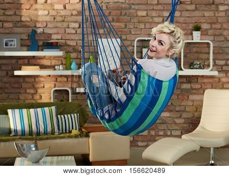Smiling young woman relaxing in hammock like chair, using tablet computer, smiling, looking at camera over shoulder.