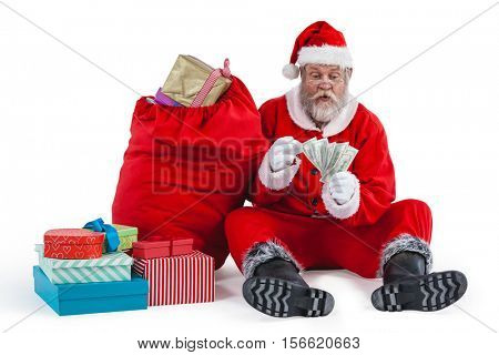 Santa claus sitting next to gift counting a currency note against white background