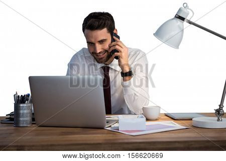 Businessman talking on mobile phone while working on laptop against white background
