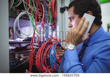 Technician talking on mobile phone while checking cables in a rack mounted server