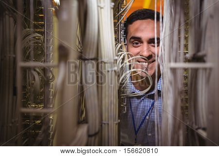 Portrait of technician analyzing server in server room