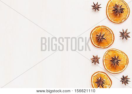 Christmas food - mulled wine background. Decorative frame of spice ingredients - anise stars cinnamon dried oranges and wine on wood white surface. Top view.