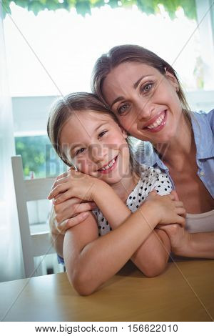Portrait of happy mother and daughter embracing at home