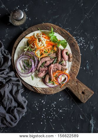 Steak tortilla with pickled carrots and cabbage on a wooden cutting board on dark background top view