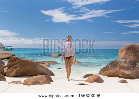 Woman wearing stylish bikini and lycra top enjoying swimming and snorkeling at amazing Anse Lazio beach on Praslin Island, Seychelles. Summer vacations on picture perfect tropical beach concept.