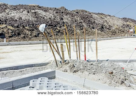 Shovels stabbed into the ground at construction site beside roadside stones.