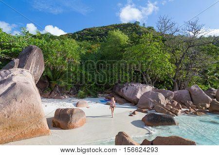 Happy woman wearing stylish bikini enjoying at amazing Anse Lazio beach on Praslin Island, Seychelles. Summer vacations on picture perfect tropical beach concept.