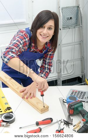 smiling young woman assembling wooden planks using screwdriver
