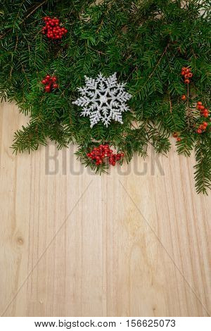 Christmas border with decorative wreath on wooden boards.