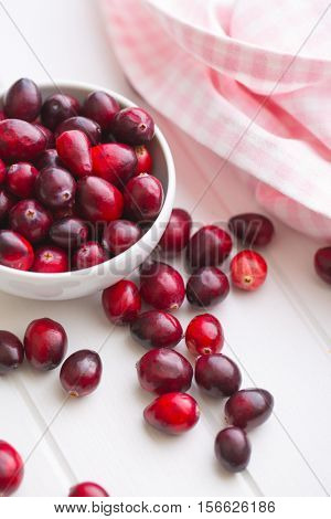 The tasty american cranberries in bowl on white table.