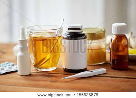 healthcare, medicine and treatment concept - drugs, thermometer, honey and cup of tea on wooden table