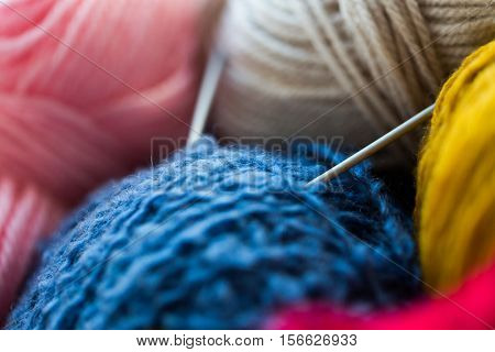 handicraft and needlework concept - close up of knitting needles and balls of yarn