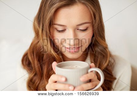 leisure, drink, winter and people concept - close up of happy young woman with cup of coffee at home