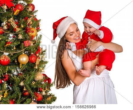 Mom wearing Santa hat holding baby with gift box under Christmas tree. First Christmas for child.