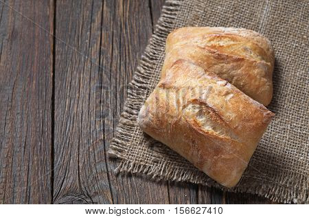 Two loaves of ciabatta bread on dark wooden table