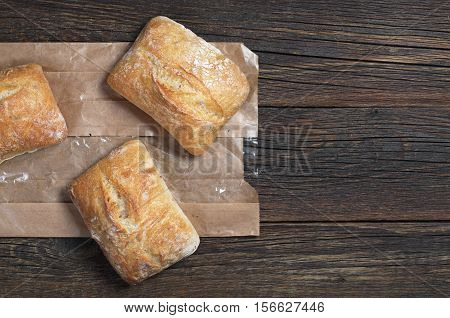 Fresh ciabatta bread on dark wooden table with paper package top view. Space for your text