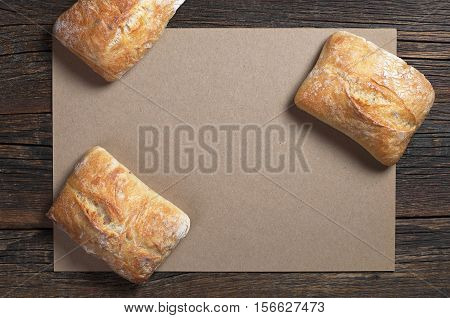 Fresh ciabatta bread on dark wooden table with empty paper top view. Space for your text