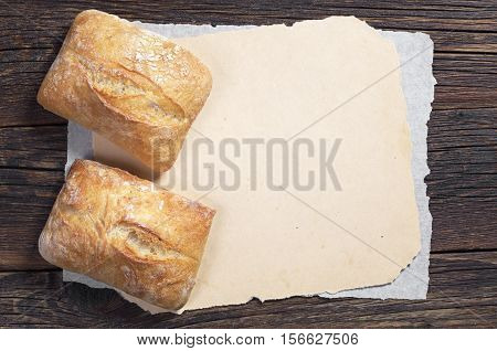Fresh ciabatta bread on dark wooden table with blank paper top view. Space for your text