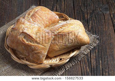 Fresh ciabatta bread in wicker plate on rustic wooden table