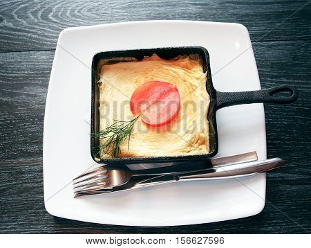 Small pan with scrambled eggs on dark wooden table
