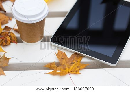 season, technology and advertisement concept - close up of tablet pc computer and coffee paper cup on bench in autumn park