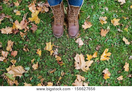 season, footwear and people concept - female feet in boots with autumn leaves on grass