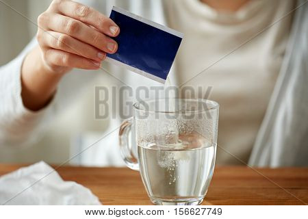 healthcare, medicine and people concept - close up of woman pouring medication into cup of water