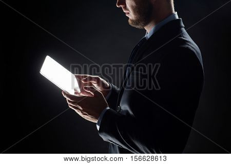 business, people and future technology concept - close up of businessman with transparent tablet pc computer over black