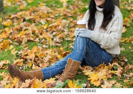 season, technology and people concept - close up of young woman drinking coffee from paper cup in autumn park