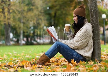 season, literature, education and people concept - young woman reading book and drinking coffee from paper cup in autumn park