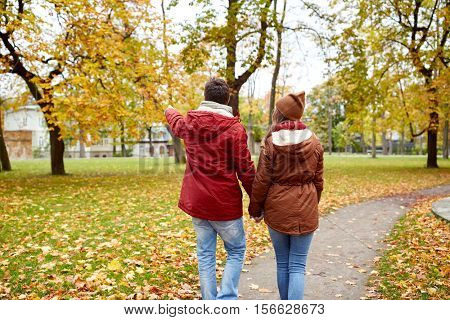 love, relationships, season and people concept - happy young couple walking in autumn park and pointing finger to something