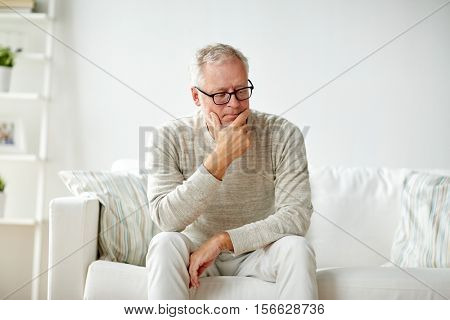 old age, problem and people concept -  senior man in glasses thinking and sitting on sofa at home