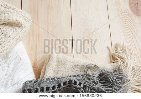 Cozy and soft winter background. Warm knitted clothes on a wooden background. Holidays at home. Selective Focus.