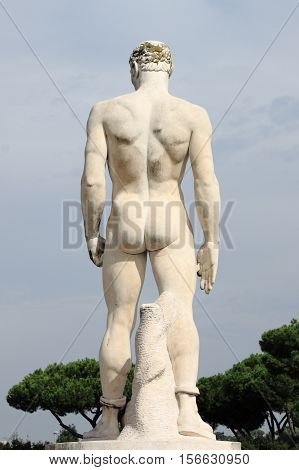 Rear side of a virile statue in the Marble Stadium of Rome, Italy