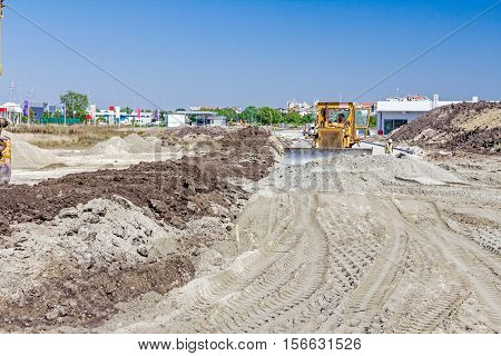 Earthmover is moving earth at building site.