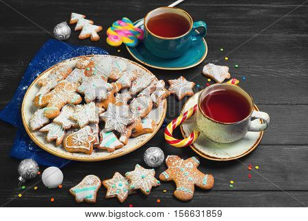 Christmas sweets baking gingerbread cookies on plate. Decorated for Christmas gingerbread cookies christmas bumps. Christmas cookies gingerbread on black table hot tea. New Year food.